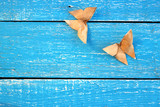 Two couple origami butterfly from coffee paper on blue wooden boards