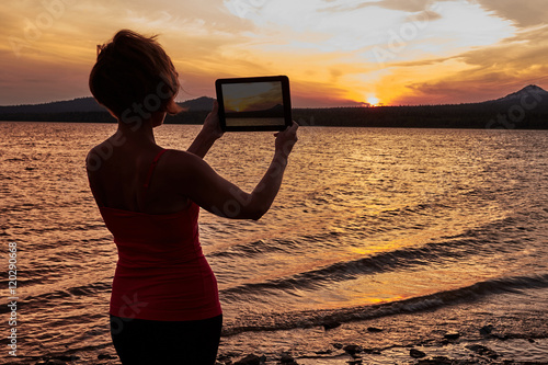 Girl photographing the sunset on the table Poster