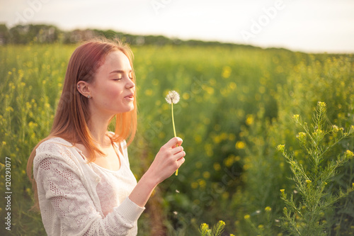 Young spring fashion woman blowing dandelion in spring garden. Springtime. Trendy girl at sunset in spring landscape background