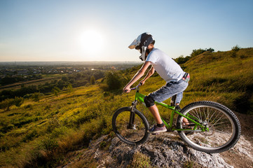 Cyclist in helmet and glasses on mountain bicycle stands on the precipice of slope and looking down under blue sky