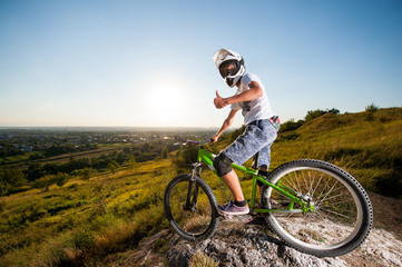 Bicyclist in helmet and glasses on mountain bike stands on the precipice of hill and showing thumb up gesture of good class under blue sky and sun. Wide angle view