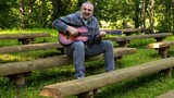 Smiling man playing guitar in park on bench