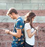 coppia di ragazzi che chattano al telefono di schiena