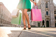 Female legs with colorful shopping bags on the main square in front of the famous duomo cathedral in Milan. Happy shopping weekend in Milan