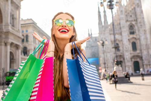 In de dag Milan Young woman with colorful shopping bags standing on the main square in front of the famous duomo cathedral in Milan. Happy shopping weekend in Milan