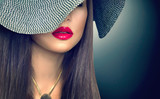 Beautiful sexy brunette woman with red lips in modern black hat