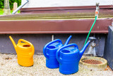 Three plastic watering cans and a garden hose.