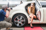 Young female celebrity posing in limousine for paparazzi on red