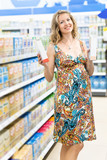 Young pregnant woman choosing milk produces at shopping in dairy supermarket store