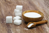 Fototapety Stack of sugar cubes and salt in wooden bowl