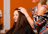 Hairdresser making hair of beautiful girl in hairdressing salon