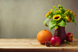 Thanksgiving holiday concept with sunflowers and pumpkin on wooden table