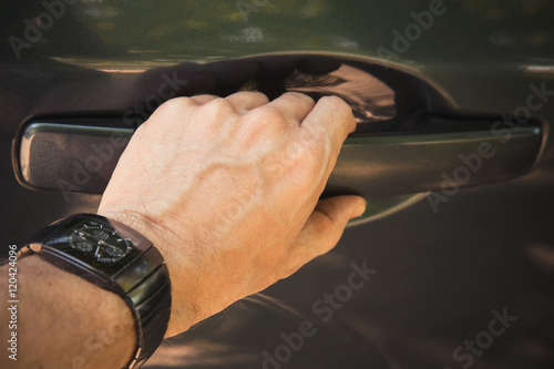 Poster Male hand with wirst watch opens car door