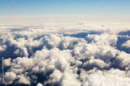 Aerial view of thick clouds over the land, the landscape. The texture of the scenic sky illuminated by the rays of the sun.