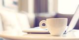 Fototapety Close up on white mug beside laptop