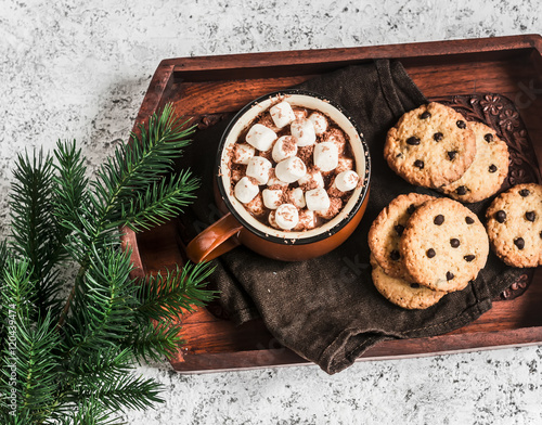 Foto op Canvas Chocolade Hot chocolate with marshmallows and chocolate chips oatmeal cookies on wooden tray on a bright background