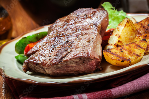 Papiers peints Steakhouse Portions of grilled beef steak with grilled potatoes and paprika