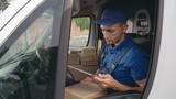 Delivery man in uniform checking packages while sitting in car and typing on digital tablet and the getting out from van