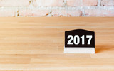 New year 2017 number on blackboard sign on wood table at brick w