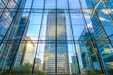 View of office buildings through glass window in Canary Wharf, London