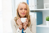 happy businesswoman drinking coffee at office