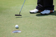 A closed up of golfer's foot hitting the golf ball into the hole