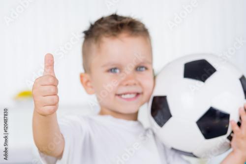 kind mit fußball zeigt daumen hoch