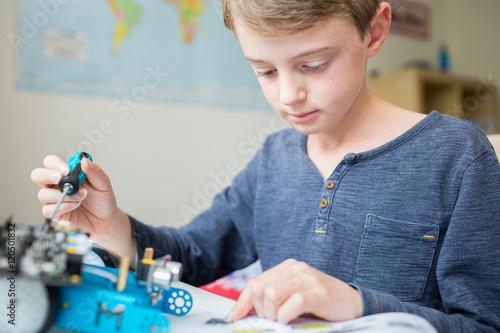 Poster Boy Assembling Robotic Kit In Bedroom