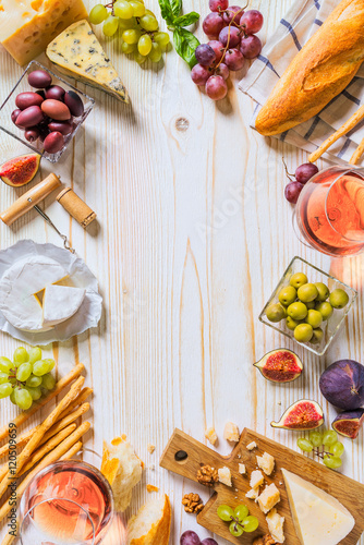 Póster Different kinds of cheeses, wine, and snacks on the white wooden