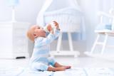 Baby boy drinking milk in sunny nursery