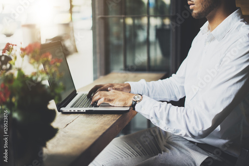 Close-up image of young professional businessman sitting at modern cafe and using laptop, confident male lawyer searching information in internet via portable computer, flare light