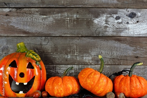 Halloween Jack o Lantern with pumpkin bottom border against a rustic old wood background
