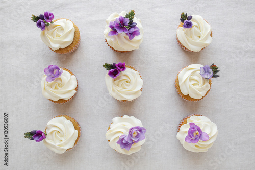 Poster Rose flower frosting vanilla cupcakes with purple edible flowers