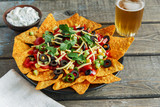 mexican tortilla chips with cheese tomato black olives pepper sauce