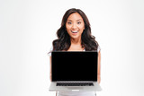 Happy smiling beautiful asian woman holding laptop with blank screen