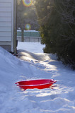 red saucer sled in winter backyard