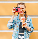 Beautiful fashionable young girl posing in a summer dress and denim jacket with pink vintage camera and multi-colored ice cream. Takes a picture. Outdoor