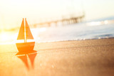 toy sailboat at the seashore during sunset