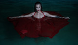 Beautiful mysterious woman looking like a vampire wearing red dress looking into the camera ehile standing in the pool at night