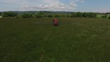 Aerial shot of tractor spraying grass seed farm