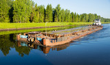 Cargo tug to the barge moves from Moscow Canal