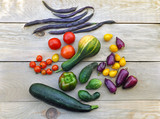 Autumn food background. Beans, tomatoes, peppers, zucchini, cucumber on light wooden surface. Top view.