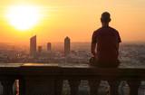 Man sitting at Fourviere Basilica, enjoying the sunrise over the city of Lyon, France.