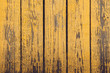 Yellow wooden planks with peeling paint