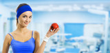 Woman in sportswear with apple, at gym