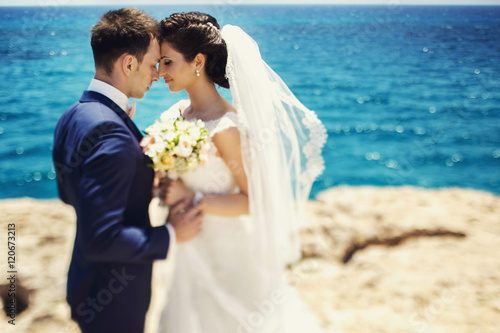 Elegant smiling young bride and groom walking on the beach