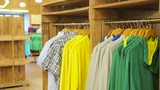 Moving clothes on the hanger in store.