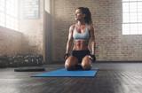 Fitness model in sportswear on exercise mat