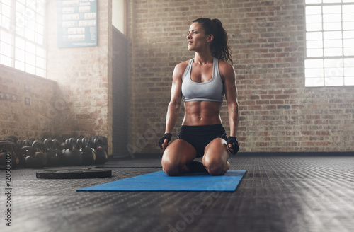 Fitness model in sportswear on exercise mat