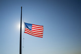 American flag flies at half mast backlit by the sun in bright blue sky - 120733498